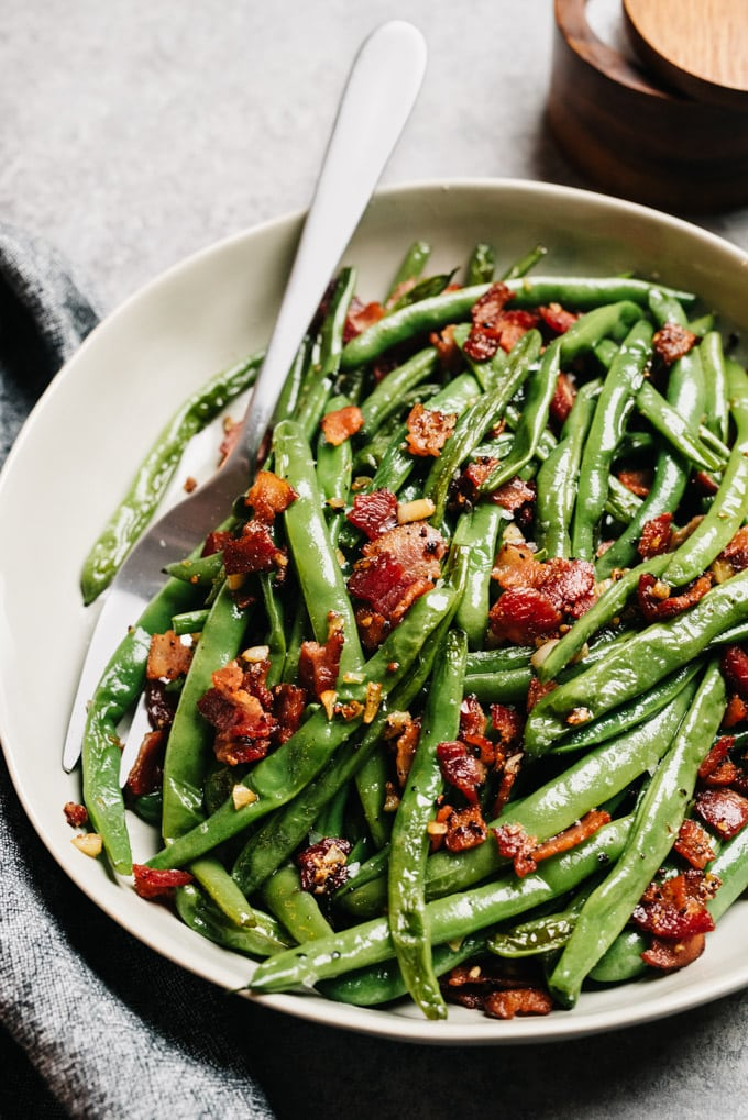 A serving bowl of green beans and bacon with a silver serving fork on a cement background with a grey linen napkin.