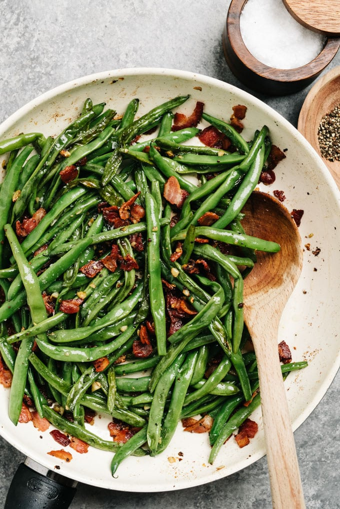A skillet of green beans cooked with bacon and garlic.