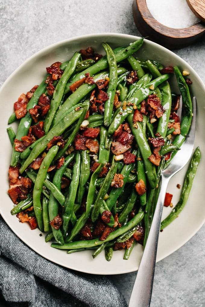 From above, green beans with bacon and garlic in a serving bowl.