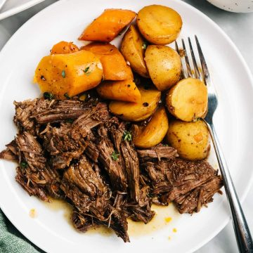 A serving of instant pot pot roast on a white plate with carrots and potatoes on a marble table.