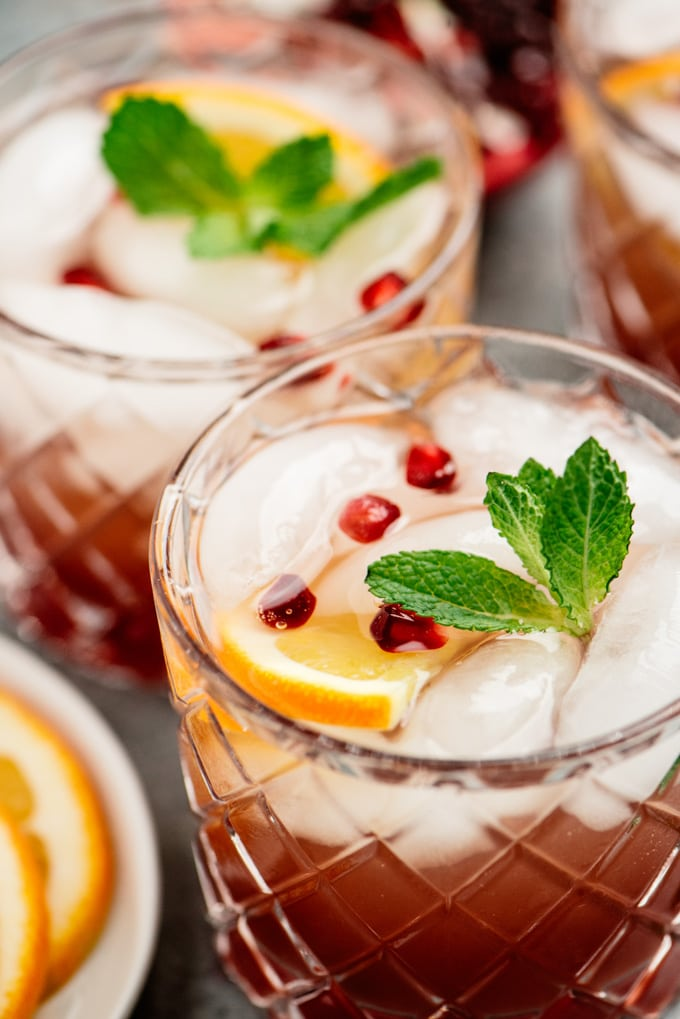 Side view, pomegranate punch Christmas cocktail with orange, pomegranate, and fresh mint garnish.