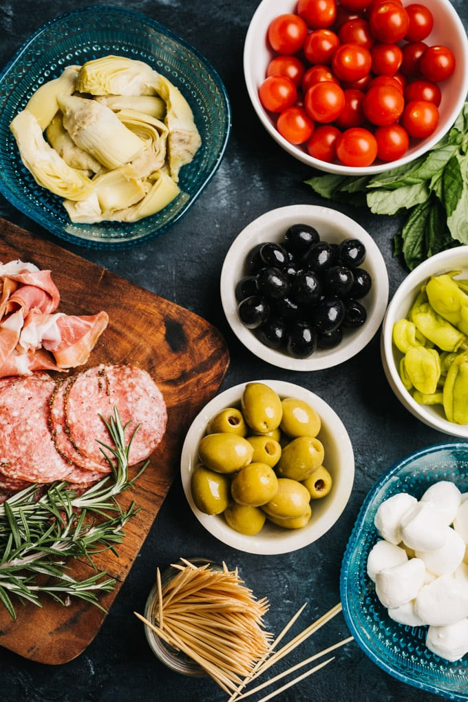 Overhead view of the ingredients for an antipasto platter on a black background.
