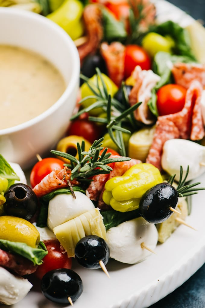 Side view, antipasto skewers on a platter served with anchovy vinaigrette.