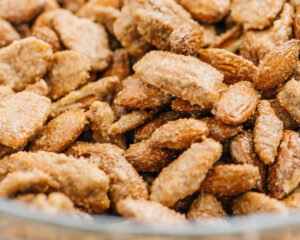 Nuts coated with egg white, sugar, and spices in a mixing bowl.