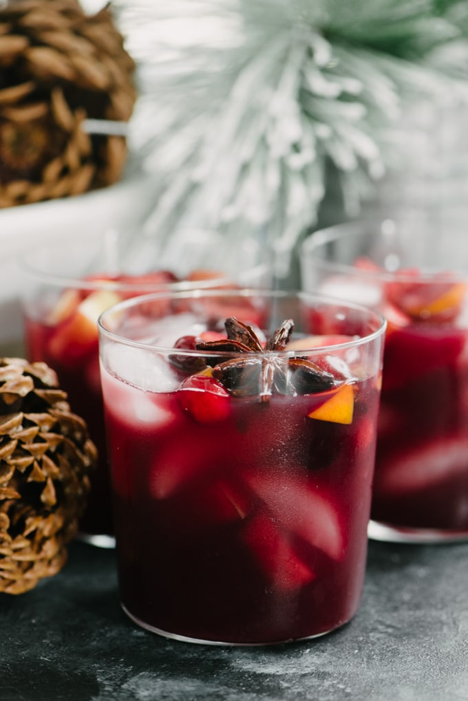 Three glasses of holiday sangria surrounded by Christmas decorations.