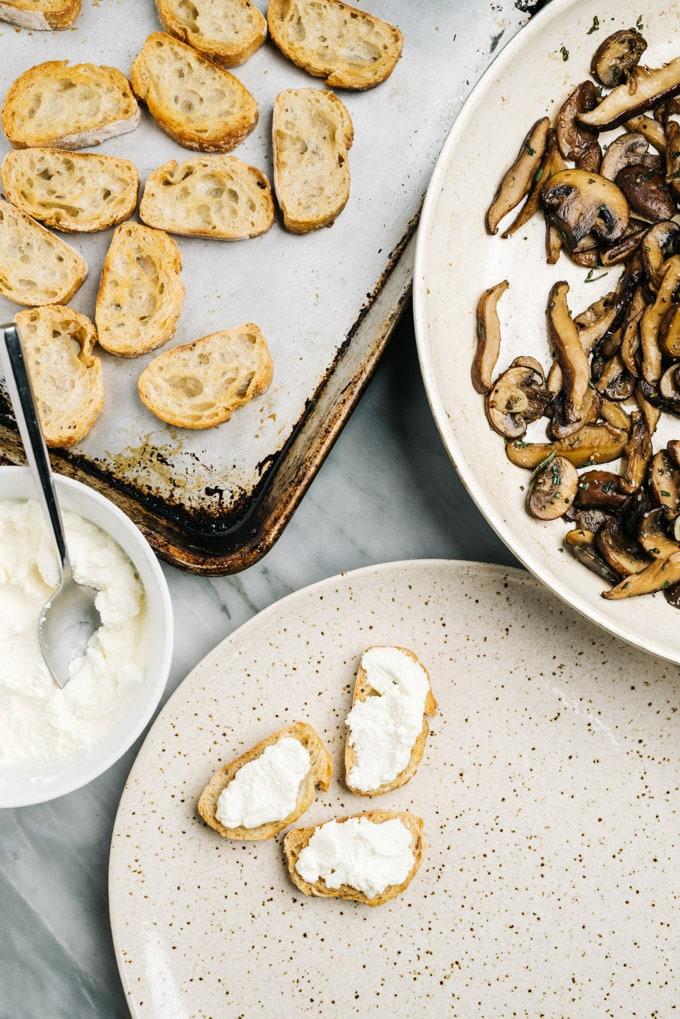 From overhead, assembling mushroom bruschetta appetizer bites.