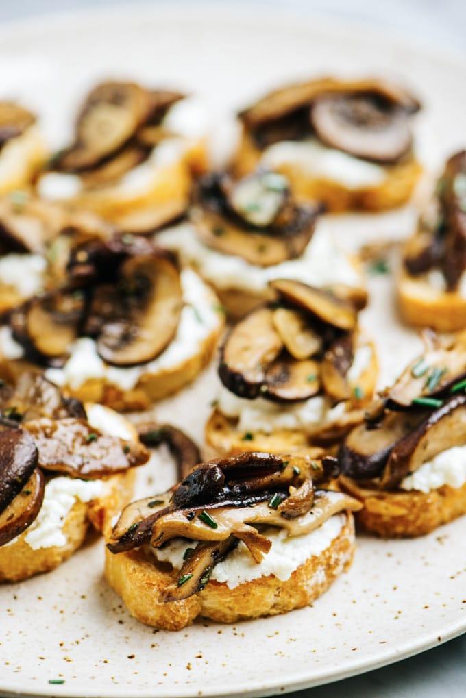 Side view, mushroom bruschetta on a speckled platter.