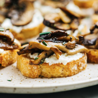 Side view, mushroom crostini on a speckled platter.