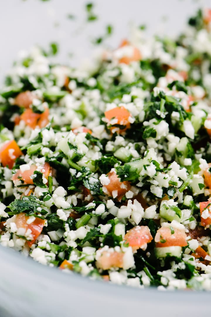 Side view, detail, grain free tabbouleh in a frosted glass bowl.
