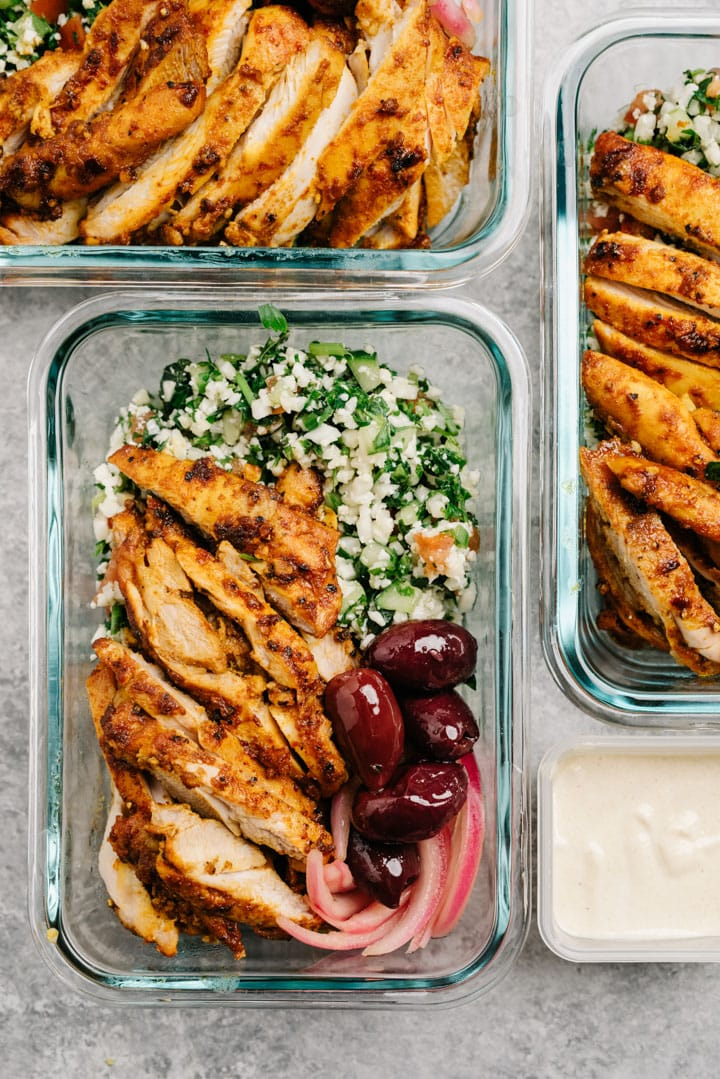 Overhead, Whole30 chicken shawarma bowls in glass meal prep containers on a cement surface.
