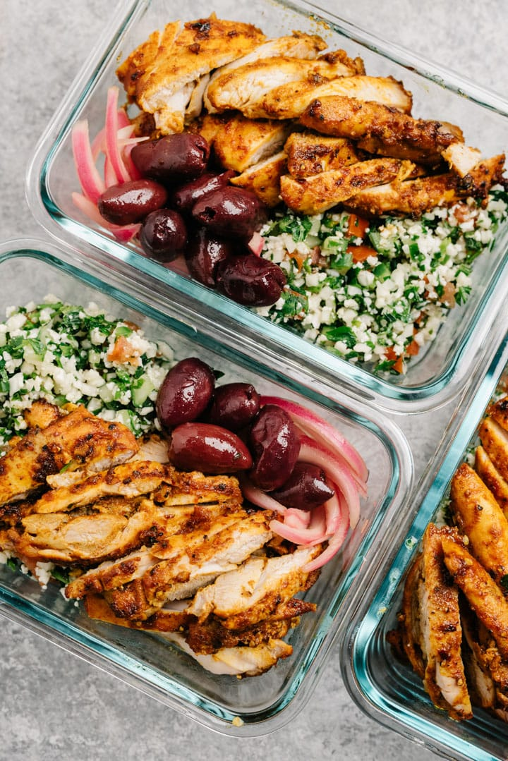 Chicken shawarma meal prep bowls with cauliflower tabbouleh, olives, and picked red onions in glass prep containers on a cement background.