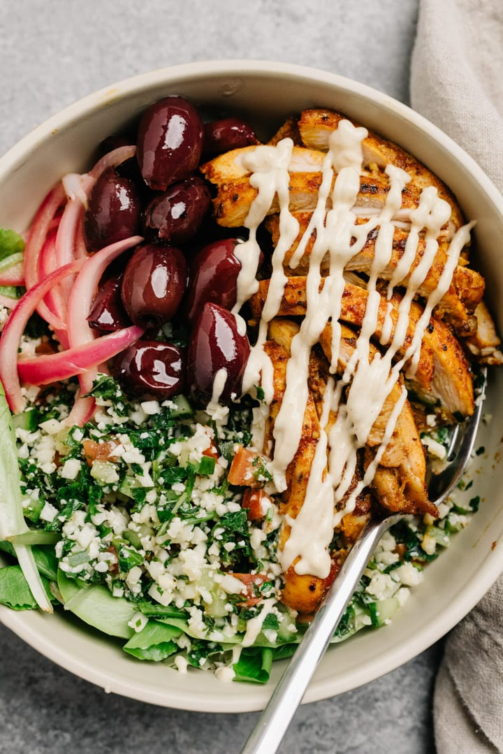 Chicken shawarma bowl with tabbouleh, olives, pickled red onions, and tahini dressing on a cement background with a tan linen napkin.