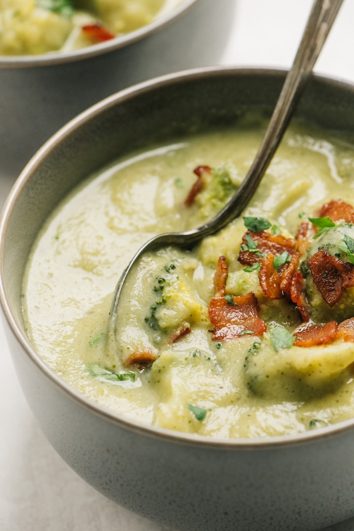 Side view, a bowl of broccoli potato soup garnished with bacon.