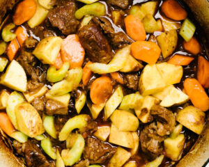 Adding carrots, celery, and potatoes to a dutch oven beef stew recipe.