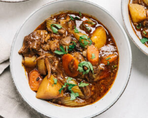 A bowl of whole30 beef stew on a cement background with a tan linen napkin.