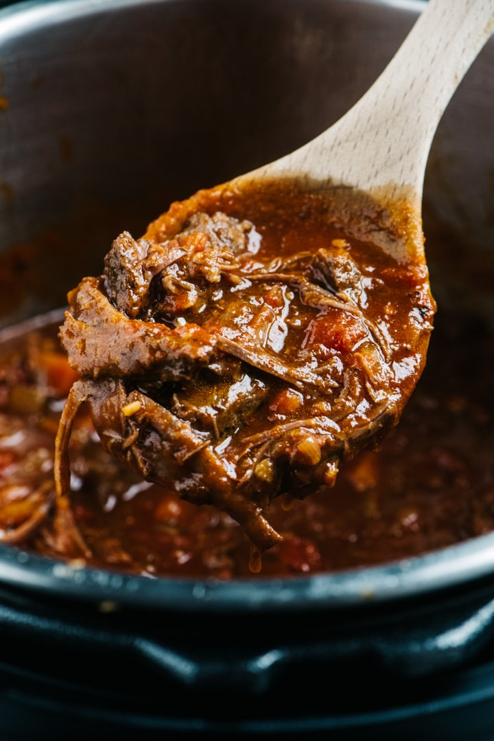 A serving of instant pot beef ragu in a wooden serving spoon.