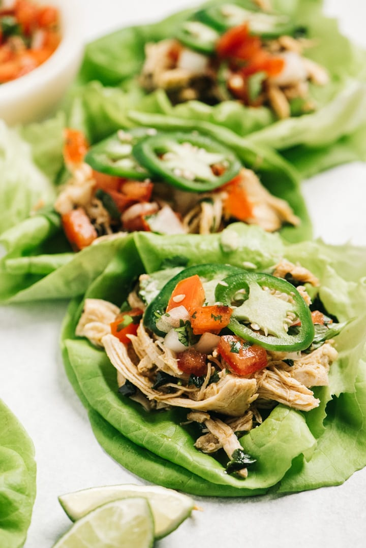 Three paleo chicken tacos made with lettuce cups and cilantro lime chicken.