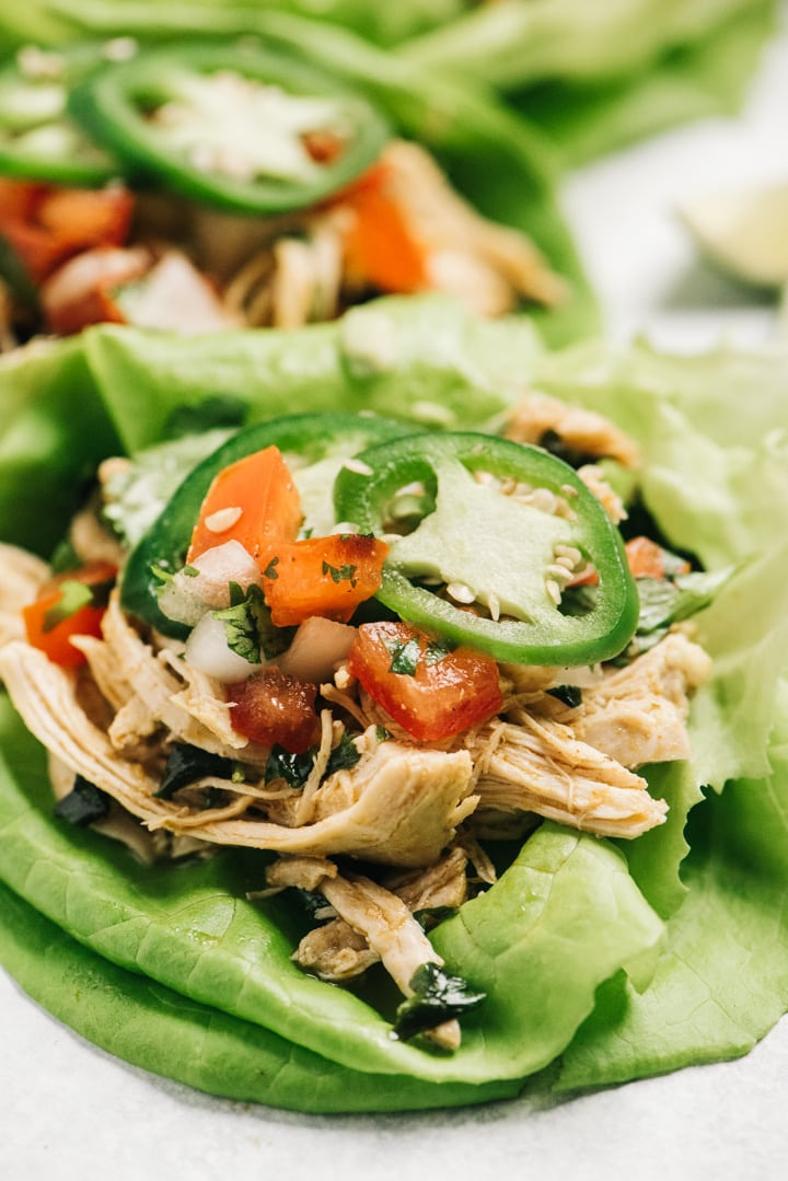 Whole30 chicken taco in a lettuce cup with shredded cilantro lime chicken.