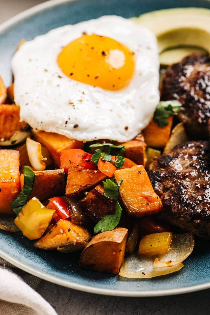 Side view, whole30 breakfast plate with sweet potato hash, sausage, and a fried egg.