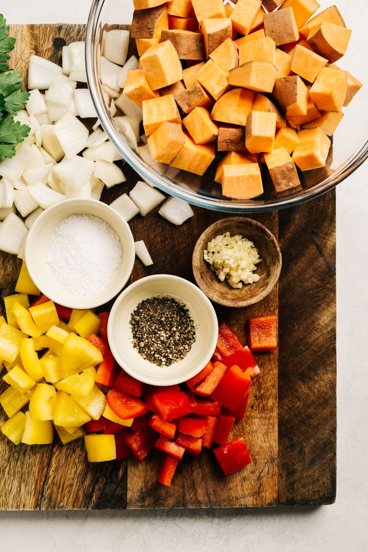 The ingredients for sweet potato hash chopped and displayed on a cutting board.