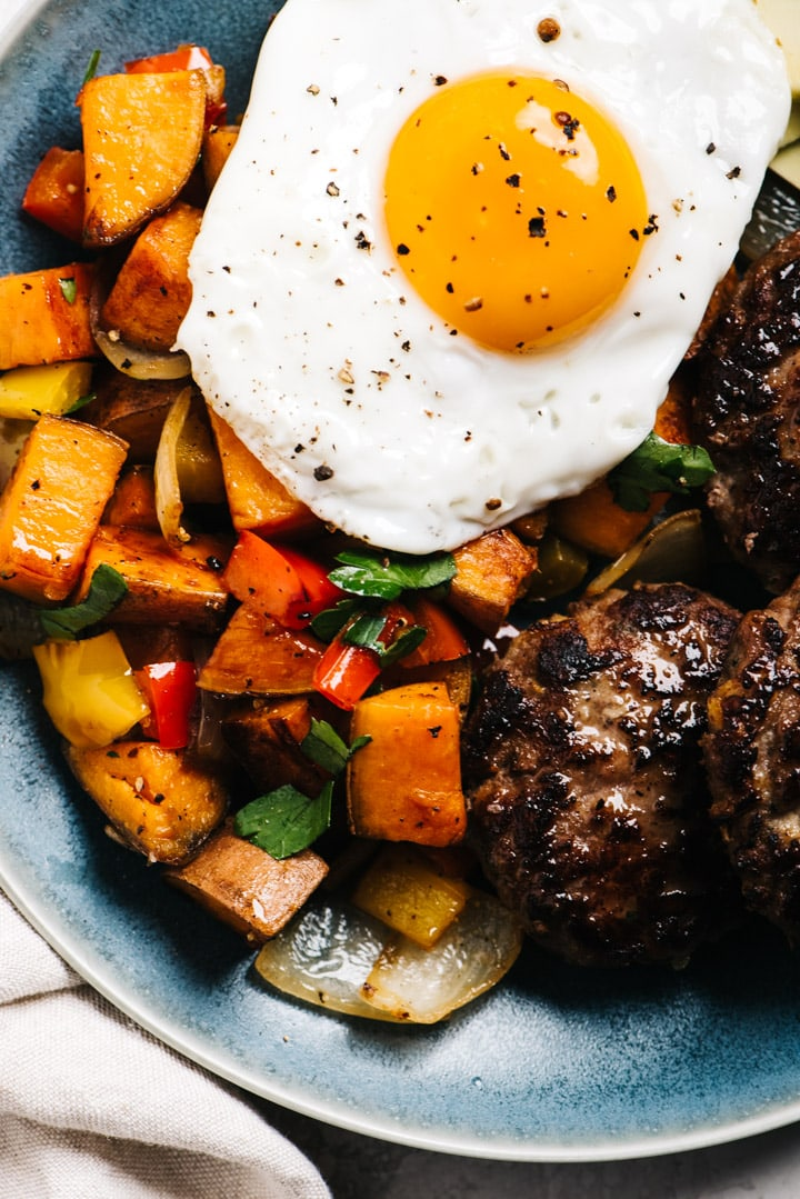 From overhead, whole30 breakfast plate with sweet potato hash, sausage, and a fried egg.