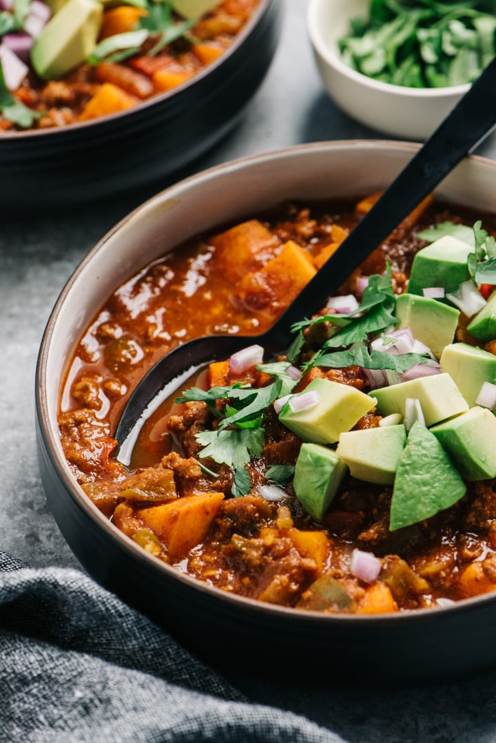 Side view, whole30 chili garnished with avocado, red onion, and cilantro.