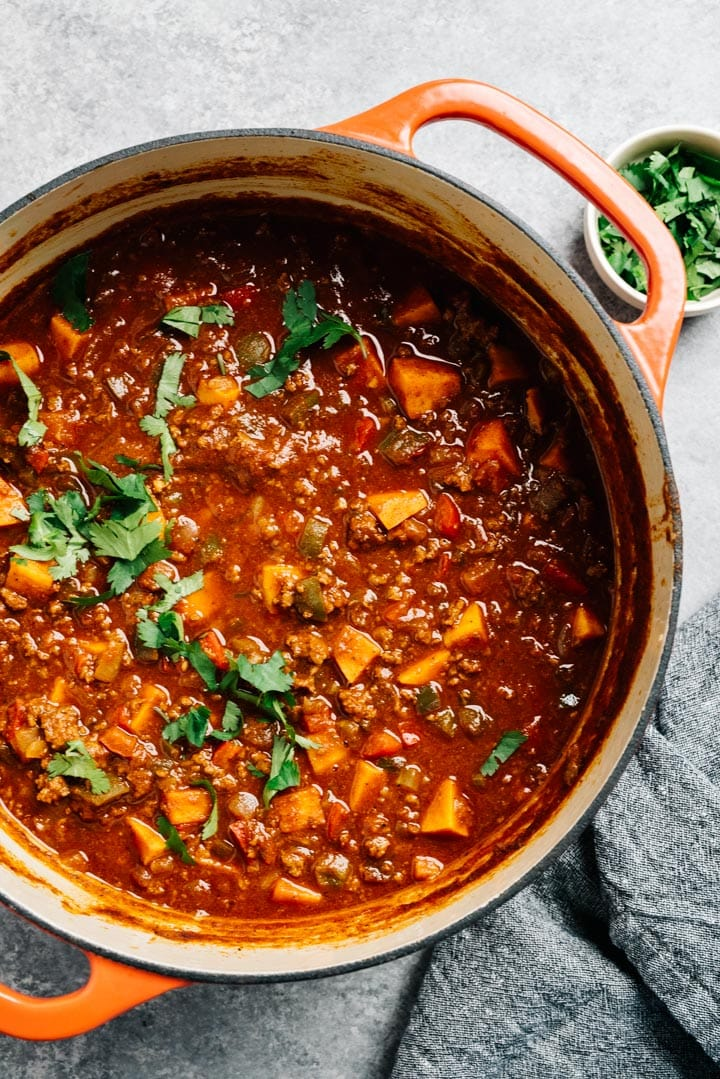 A dutch oven of whole30 beef chili with fresh cilantro.