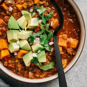 A bowl of beef and sweet potato whole30 chili on a cement background with a black soup soon.