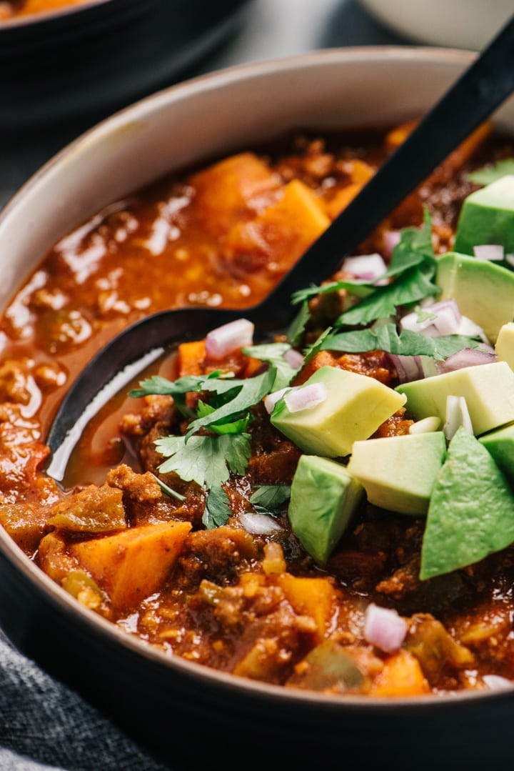 Side view, a bowl of healthy beef chili with sweet potato and extra vegetables.
