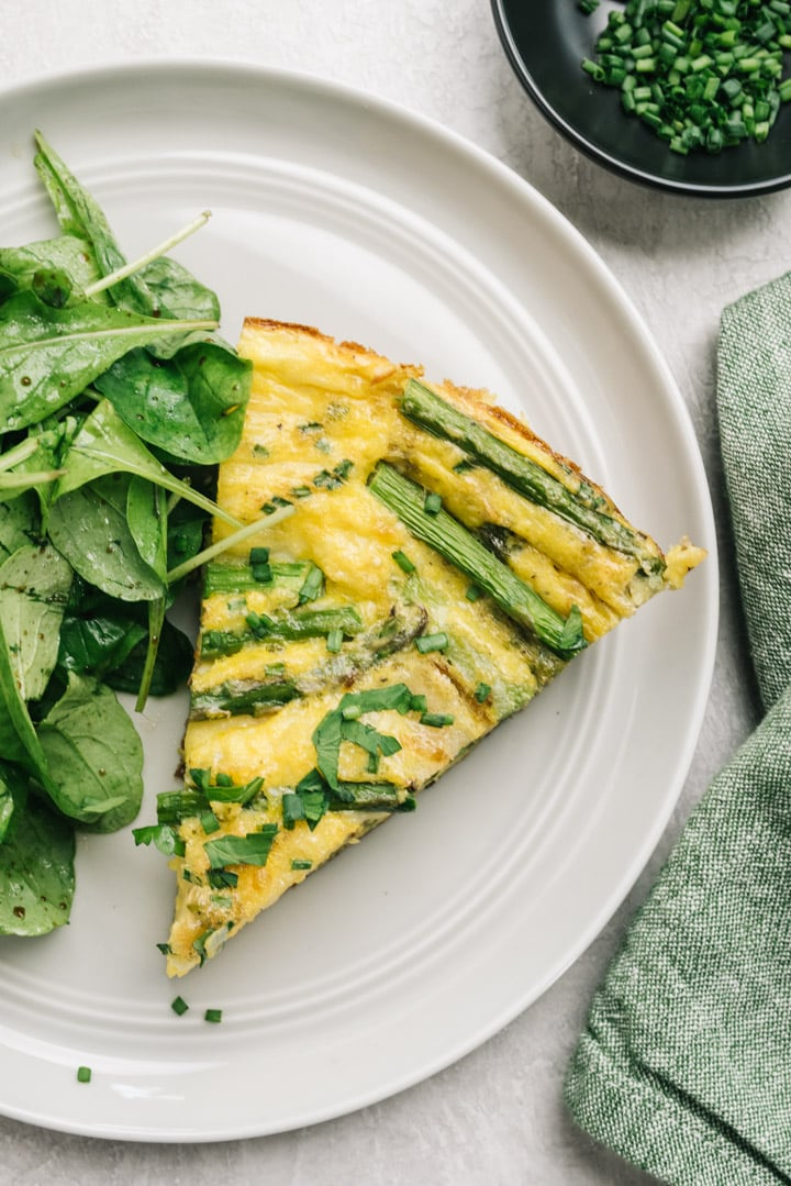 A slice of asparagus fritata on a white plate served with spinach