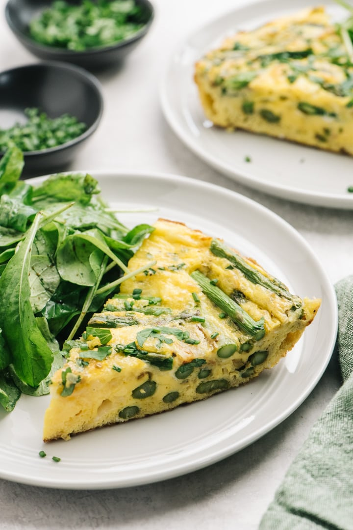 Two slices of the frittata served on plates with a simple side salad