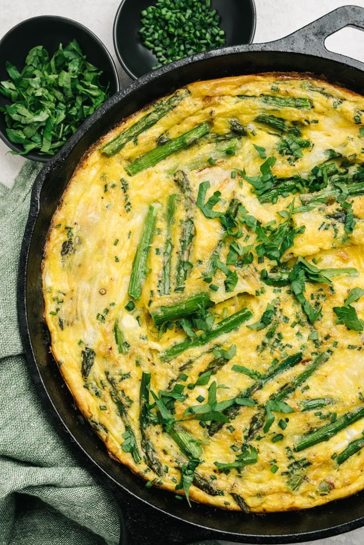 The cooked asparagus frittata in a cast iron skillet