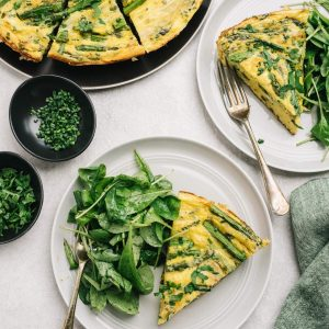 Two slices of asparagus frittata with an arugula side salad on a dining table.