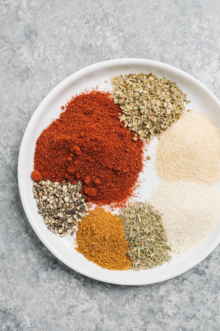 The spices for the seasoning on a white plate