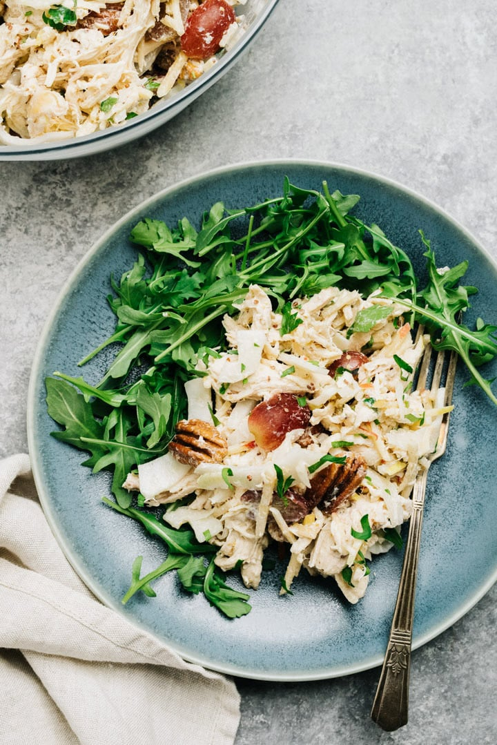 Shredded chicken salad with apple, fennel, and yogurt dressing over arugula on a blue plate.