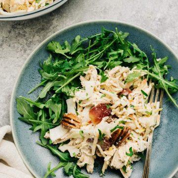 Shredded chicken salad with apple, fennel, and yogurt dressing over arugula on a blue plate.