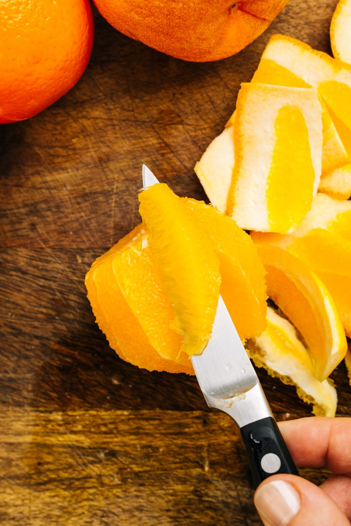 A section of orange on a paring knife.
