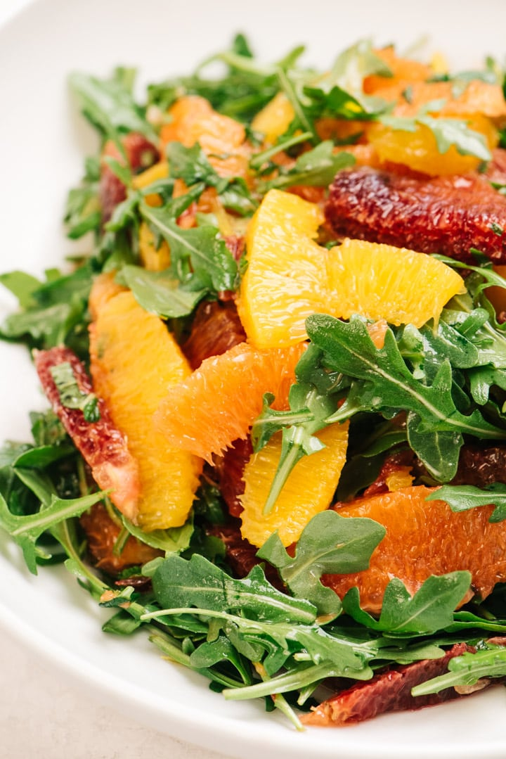Side view, citrus salad with a variety of oranges tossed with arugula and fresh mint.
