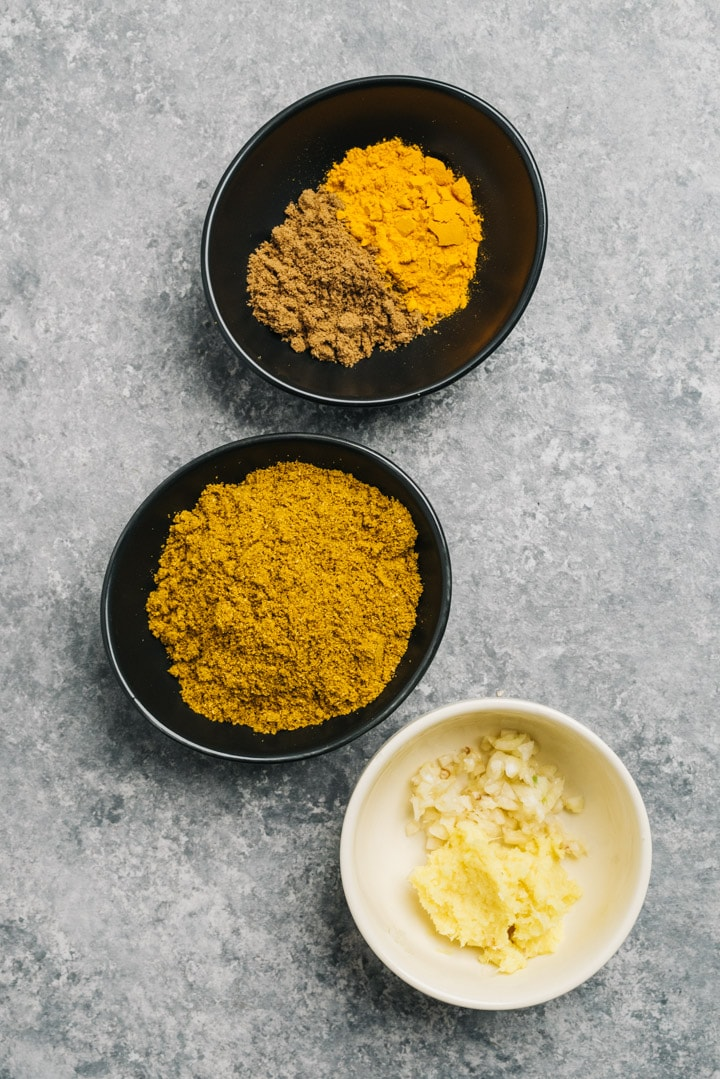 Curry powder, cumin, turmeric, garlic an ginger in small bowls on a cement background.