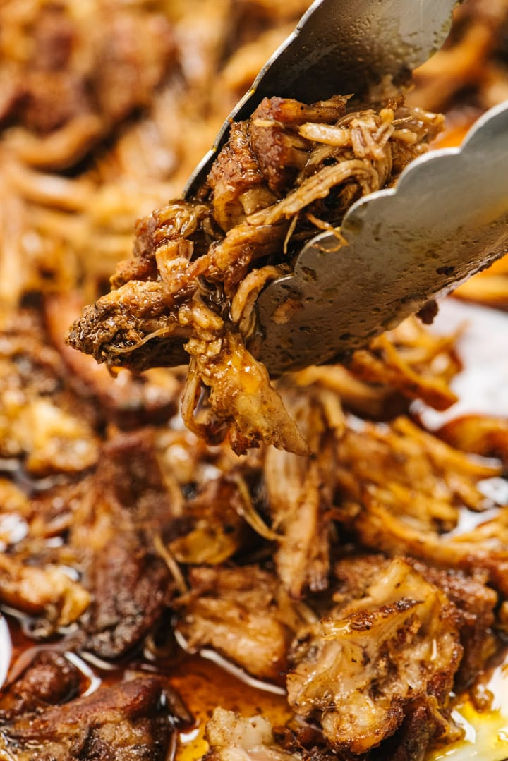 Tongs holding a serving of pulled pork cooked in the instant pot.
