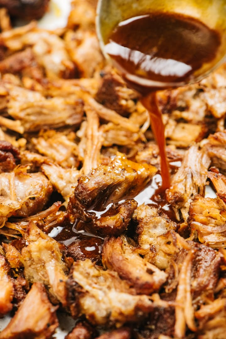 A ladle drizzling sauce over crispy shreds of pulled pork.