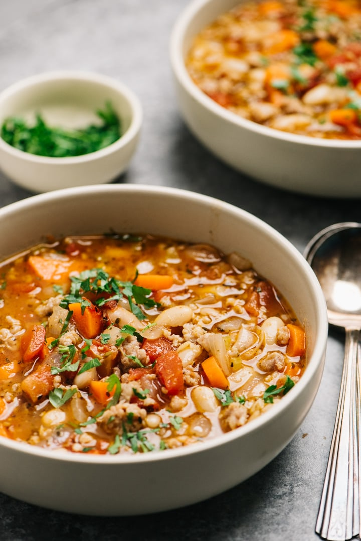Side view, two bowls of italian sausage soup with white beans, tomatoes, and vegetables on a cement background.