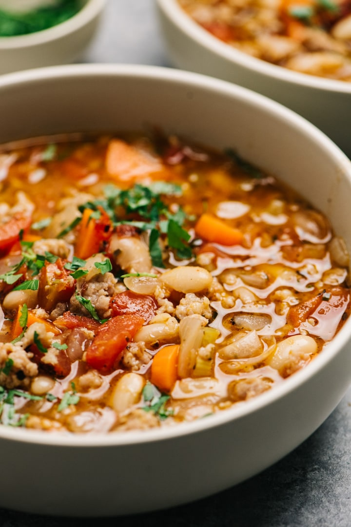 Side view, a bowl of white bean sausage soup with tomatoes and vegetables.