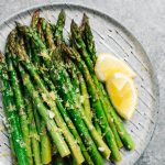 Lemon garlic asparagus on a grey speckled plate.