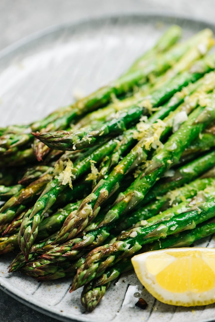 Side view, lemon garlic asparagus on a grey plate with a lemon wedge on the side.