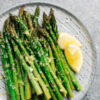 Lemon garlic asparagus on a grey speckled plate.