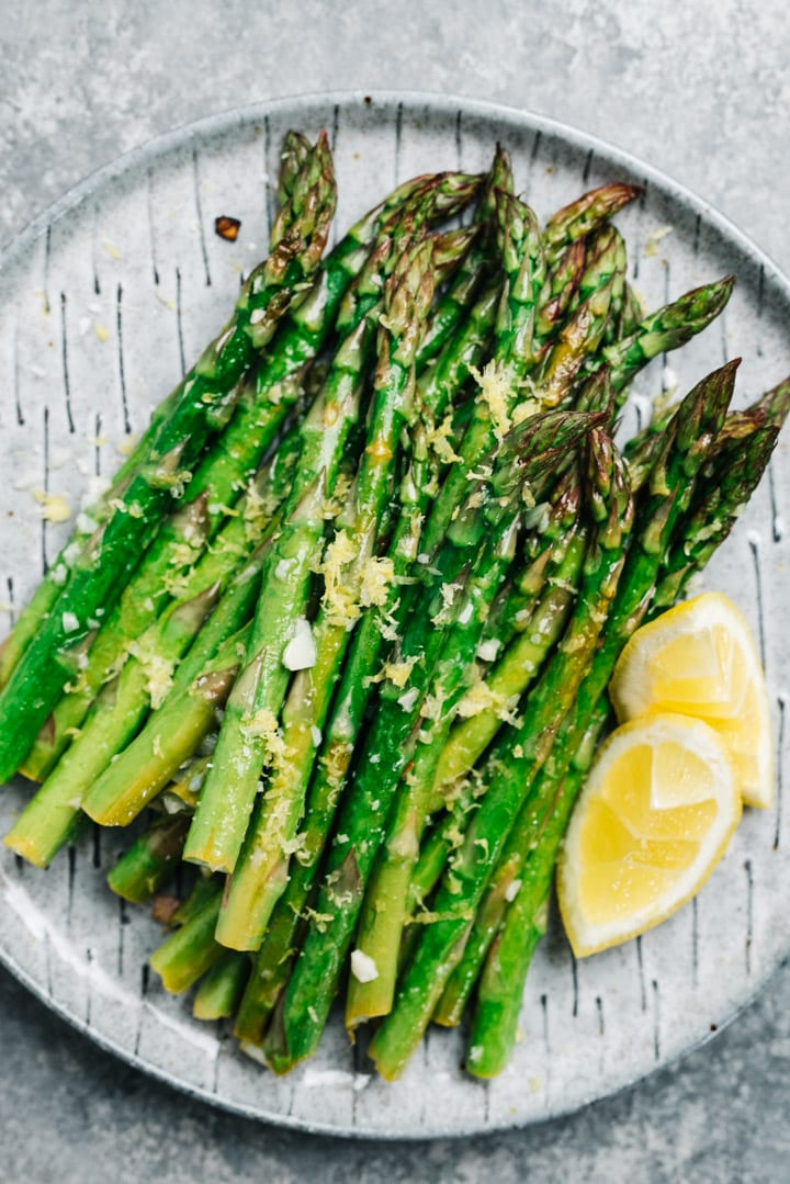 Oven roasted lemon asparagus on a grey plate with two lemon wedges.