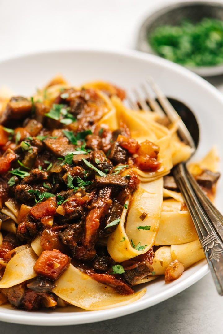Mushroom bolognese served with pappardelle in a white bowl