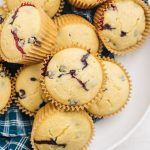 Blueberry cornbread muffins in a large white bowl lined with a blue kitchen towel.