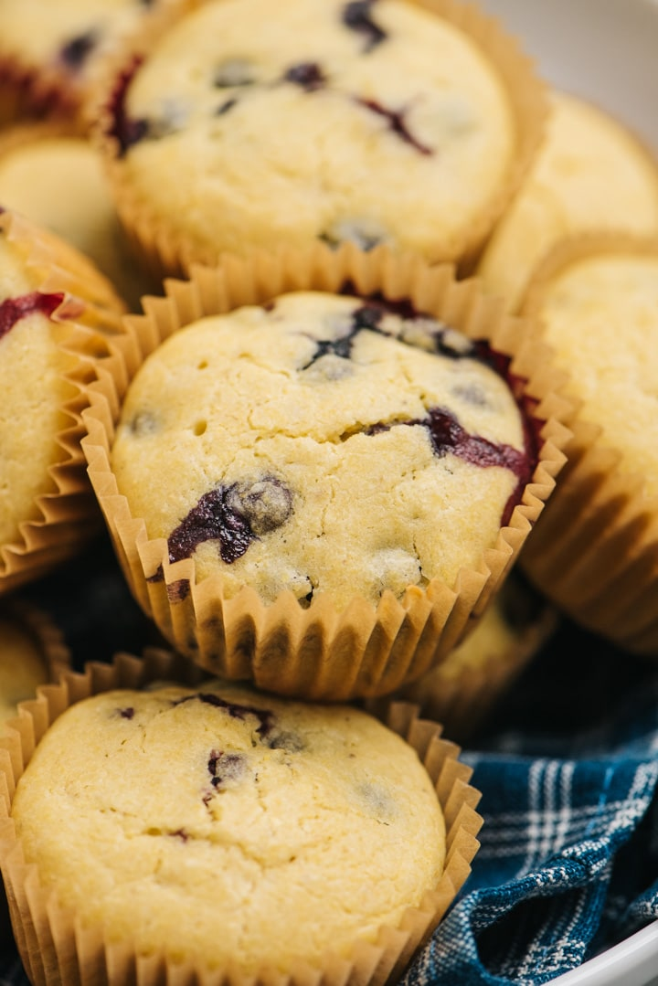 Side view, cornbread muffins with blueberries piled in a bowl.